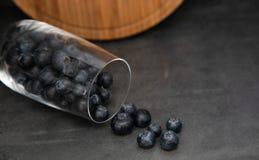 Nya bl?b?r i en glass bunke Läckra blåbär spridda från en exponeringsglaskopp Grå bakgrund i bakgrunden är ett trä royaltyfria bilder