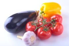 Nya blandade grönsaker aubergine, spansk peppar, tomat, vitlök bakgrund isolerad white Selektivt fokusera Arkivfoton