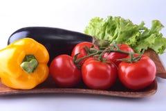 Nya blandade grönsaker, aubergine, spansk peppar, tomat, vitlök med bladgrönsallat bakgrund isolerad white Arkivbild
