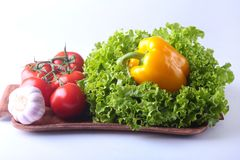 Nya blandade grönsaker spansk peppar, tomat, vitlök med bladgrönsallat bakgrund isolerad white Selektivt fokusera Royaltyfri Fotografi