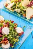 Nya blandninggrönsaksallader på den glass plattan på blå träbakgrund, produktfotografi för restaurang eller sund livsstil Arkivbild