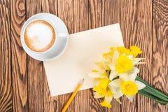 Nya blommor för vårgulingpåskliljor och tömmer etiketten på brunt målade träplankor Selektivt fokusera placera text Royaltyfri Bild
