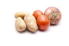 Nya bruna potatisar med tomater och löken Arkivbilder