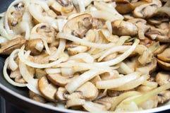 Nya champignons och l?kar stekas i en panna N?rbild royaltyfri fotografi