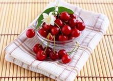 Nya Cherry i en glass kopp med jasminen blommar Arkivbild