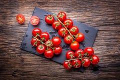 Nya Cherry Tomatoes Mogna tomater på ekträbakgrund Arkivbild