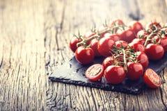 Nya Cherry Tomatoes Mogna tomater på ekträbakgrund Arkivfoton