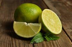 Nya citron och limefrukter på brun träbakgrund Arkivbilder
