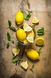 Nya citroner i en hink av sidor trägrund tabell för djupfält Royaltyfri Foto