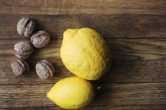 Nya citroner och muttrar på träbackrounden, ingredienser, fres Arkivbild