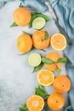 Nya clementines med gröna sidor och limefrukt med en kniv Arkivbild