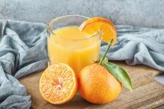 Nya clementines ombord med gröna sidor och fruktsaftexponeringsglas Fotografering för Bildbyråer