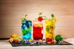 Nya coctailar med mintkaramellen, limefrukt, is, bär och carambolaen på en ljus träbakgrund Uppfriskande sommardrycker kopiera av Royaltyfri Fotografi