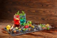 Nya coctailar med mintkaramellen, limefrukt, is, bär och carambolaen på träbakgrunden Uppfriskande sommardrycker kopiera avstånd Royaltyfri Bild