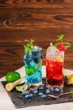 Nya coctailar med mintkaramellen, limefrukt, is, bär och carambolaen på träbakgrunden Uppfriskande sommardrycker kopiera avstånd Arkivbilder