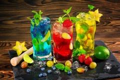 Nya coctailar med mintkaramellen, limefrukt, is, bär och carambolaen på träbakgrunden Uppfriskande sommardrycker kopiera avstånd Arkivfoto