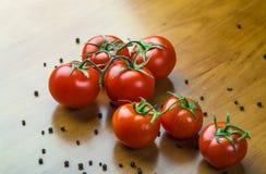 Nya druvatomater med kryddor för bruk som matlagningingredienser på trätabellen Arkivbild