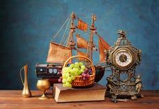 Nya druvor i en vide- korg och en klocka Arkivbild