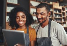 Nya företagsägare som använder minnestavlan i kafé royaltyfria foton