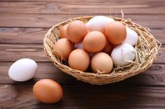 Nya fega ägg i korg på brun bakgrund royaltyfria bilder