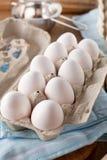 Nya fega ägg på den mörka trätabellen arkivbild