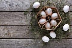 Nya fega vita ägg i låda på lantlig wood bakgrund Fotografering för Bildbyråer
