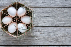 Nya fega vita ägg i låda på lantlig wood bakgrund Royaltyfri Foto