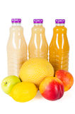 Nya flaskor av fruktsaft med frukter som isoleras på vit Arkivbild