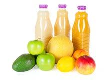 Nya flaskor av fruktsaft med frukter som isoleras på vit Royaltyfri Bild