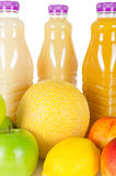 Nya flaskor av fruktsaft med frukter som isoleras på vit Royaltyfria Bilder