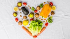 Nya frukt och grönsaker, korn och muttrar på en vit bakgrund i form av hjärta Arkivfoto