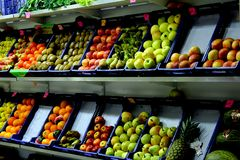 Nya frukt och grönsaker på hyllorna av en greengroccer shoppar royaltyfria foton