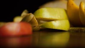 Nya frukter över svart bakgrund Nya läckra skivade frukter faller på tabellen på en svart bakgrund, begrepp av Royaltyfri Foto