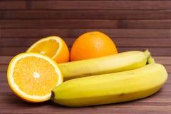 Nya frukter banan, apelsin som isoleras på träbakgrund Royaltyfria Foton