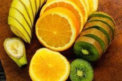 Nya frukter banan, kiwi, apelsin på träbakgrund sund mat ny fruktmix Grupp av citrusfrukter Rå vegetarian Royaltyfri Fotografi