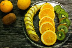 Nya frukter banan, kiwi, apelsin på träbakgrund sund mat ny fruktmix Grupp av citrusfrukter Rå vegetarian Royaltyfria Bilder