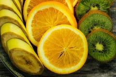 Nya frukter banan, kiwi, apelsin på träbakgrund sund mat ny fruktmix Grupp av citrusfrukter Rå vegetarian Royaltyfria Foton