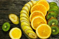 Nya frukter banan, kiwi, apelsin på träbakgrund sund mat ny fruktmix Grupp av citrusfrukter Rå vegetarian Arkivbild