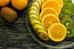 Nya frukter banan, kiwi, apelsin på träbakgrund sund mat ny fruktmix Grupp av citrusfrukter Rå vegetarian Royaltyfri Foto