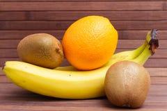 Nya frukter banan, kiwi, apelsin som isoleras på träbakgrund Royaltyfri Fotografi