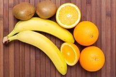 Nya frukter banan, kiwi, apelsin som isoleras på träbakgrund Royaltyfria Foton