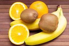 Nya frukter banan, kiwi, apelsin som isoleras på träbakgrund Fotografering för Bildbyråer