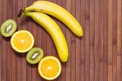 Nya frukter banan, kiwi, apelsin som isoleras på träbakgrund Arkivbild