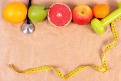 Nya frukter, cm, stetoskop och hantlar för kondition, begrepp av sunda livsstilar Royaltyfria Bilder