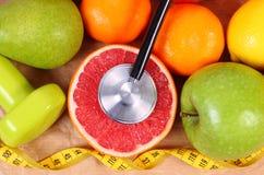 Nya frukter, cm, stetoskop och hantlar för kondition, sunda livsstilar Royaltyfri Bild