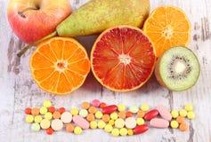 Nya frukter och färgrika medicinska preventivpillerar, val mellan sund näring och läkarundersökningtillägg Arkivbild