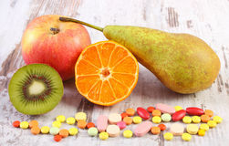 Nya frukter och färgrika medicinska preventivpillerar, val mellan sund näring och läkarundersökningtillägg Royaltyfri Foto