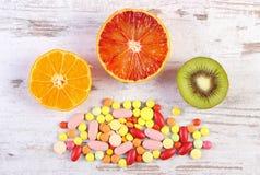 Nya frukter och färgrika medicinska preventivpillerar, val mellan sund näring och läkarundersökningtillägg Royaltyfria Bilder