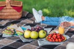 Nya frukter och smörgåsar på plädet och personen som bakom dricker fruktsaft Arkivfoton