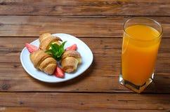 Nya giffel och ett exponeringsglas av orange fruktsaft på en trätabell Royaltyfria Bilder
